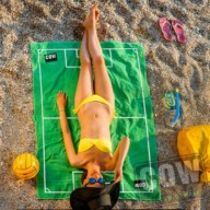 Woman in swimsuit and hat lying on the green towel on the beach. Top view